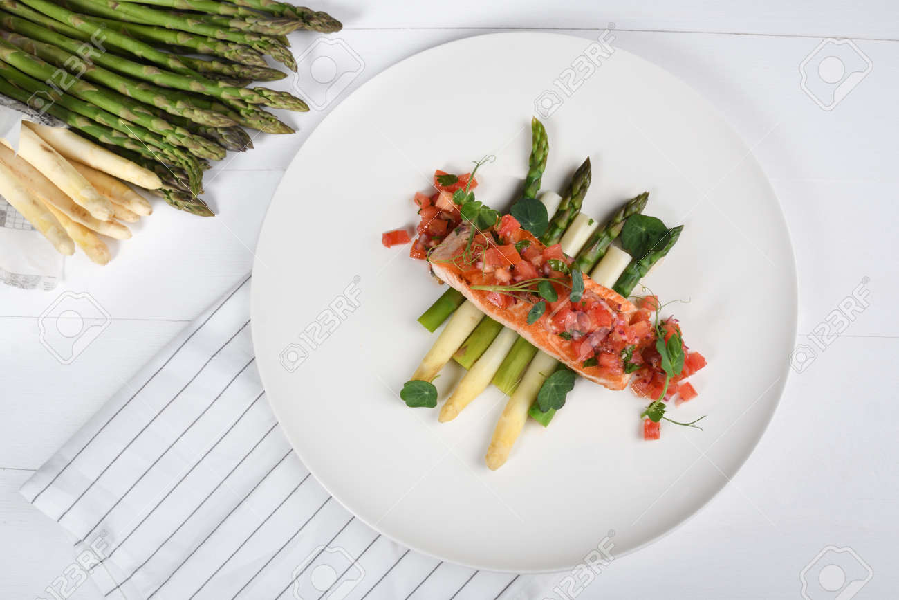 Grilled salmon fillet and white and green fresh asparagus. Healthy eating concept. Chopped tomatoes on top, studio shot - 146881106