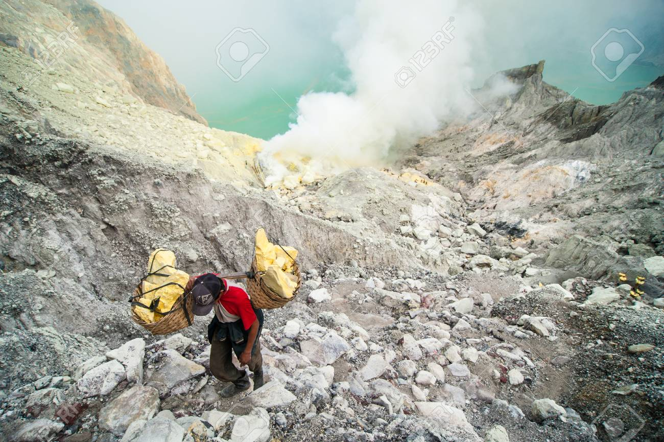 Worker at Kawah Ijen sulfer mine carries a basket of sulfur out of the crater Standard-Bild - 43483855