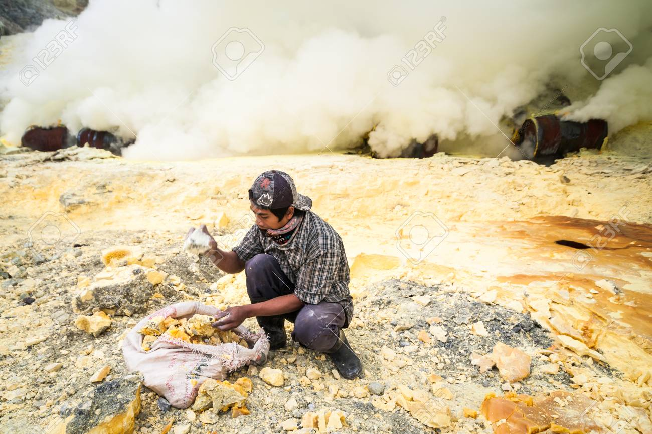 Worker at gunung Ijen in Java, Indonesia collecting sulfur Standard-Bild - 43483536