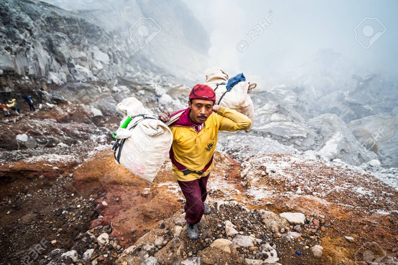 Miner at Kawah Ijen in Java, Indonesia carries sulfer out of the crater Standard-Bild - 43483535