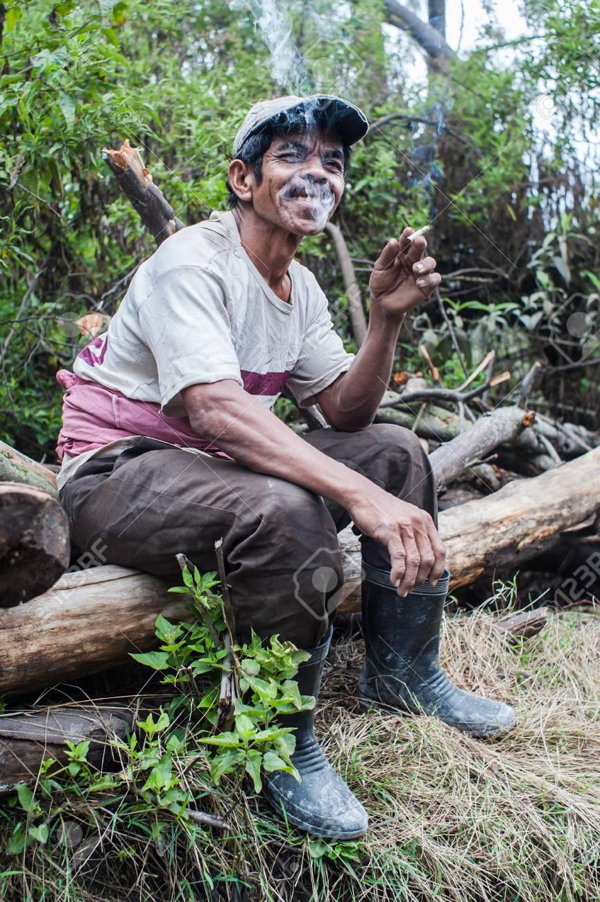 Worker at Kawah Ijen takes a break and smokes Standard-Bild - 43483527