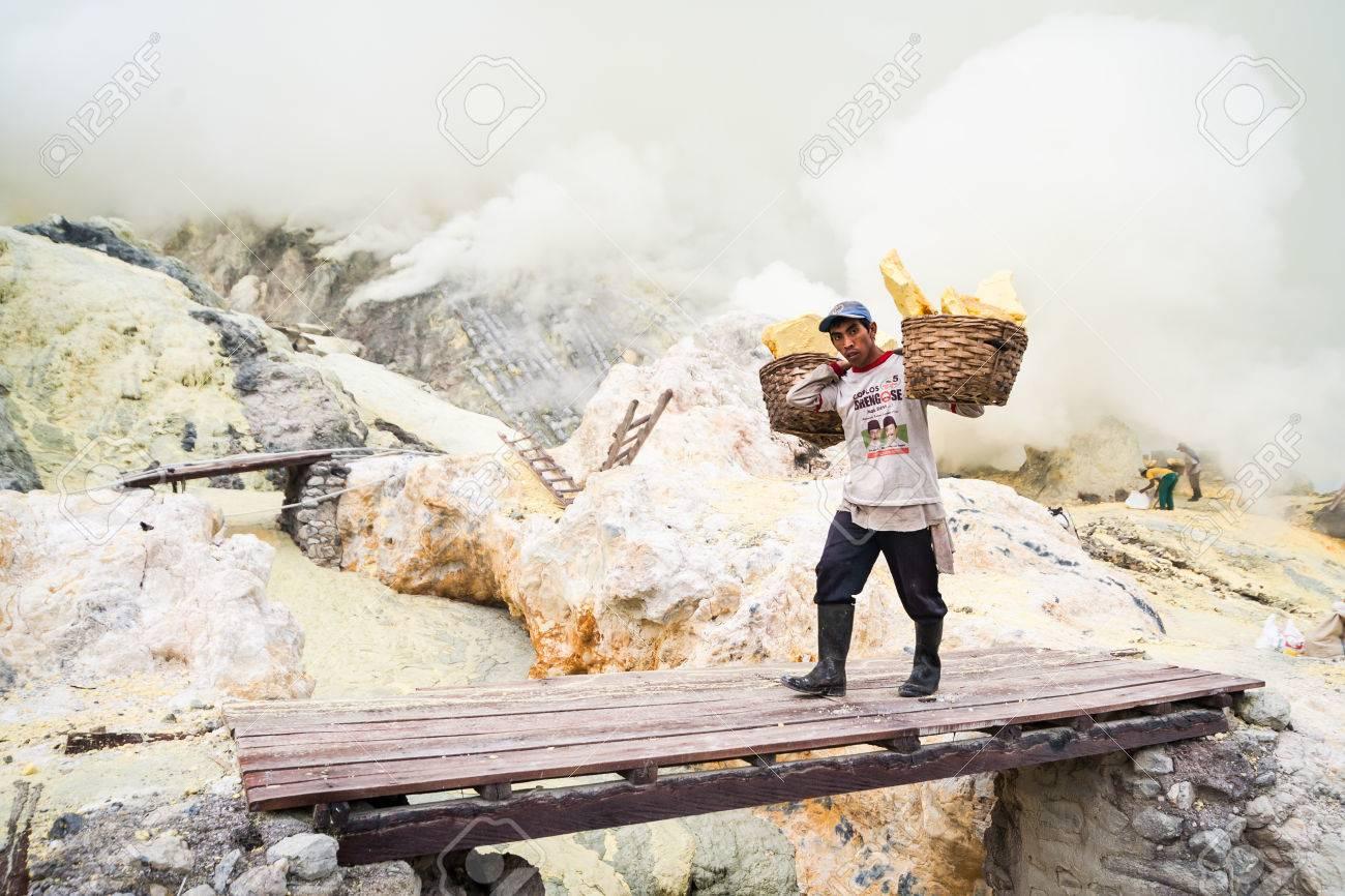 Worker at Kawah Ijen in Java, Indonesia carries sulfur Standard-Bild - 43483375