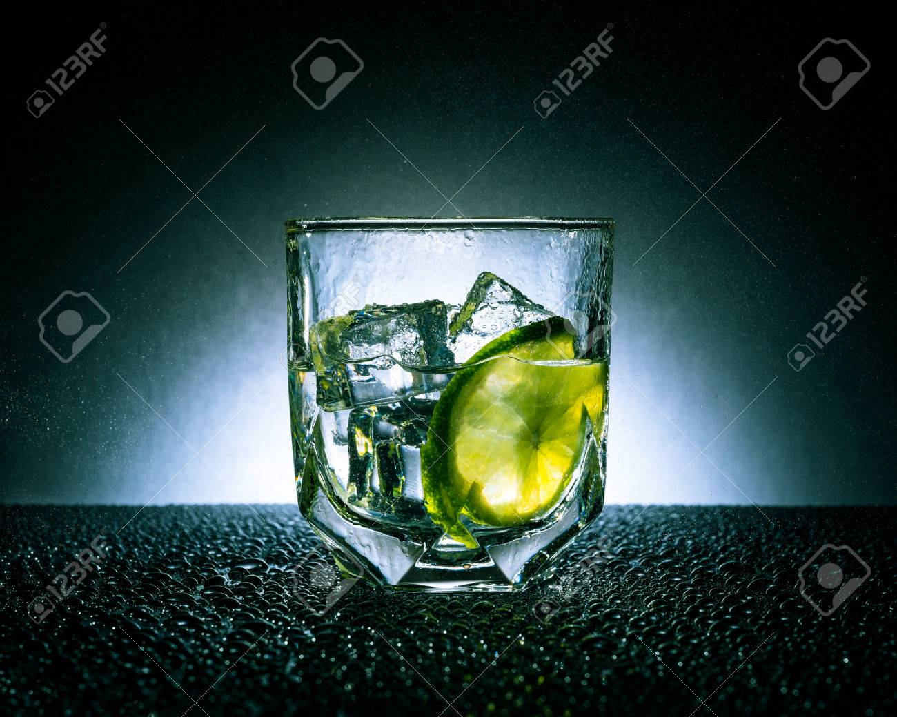 Gin and tonic with ice and lime on a dark background with white spot Standard-Bild - 41174285