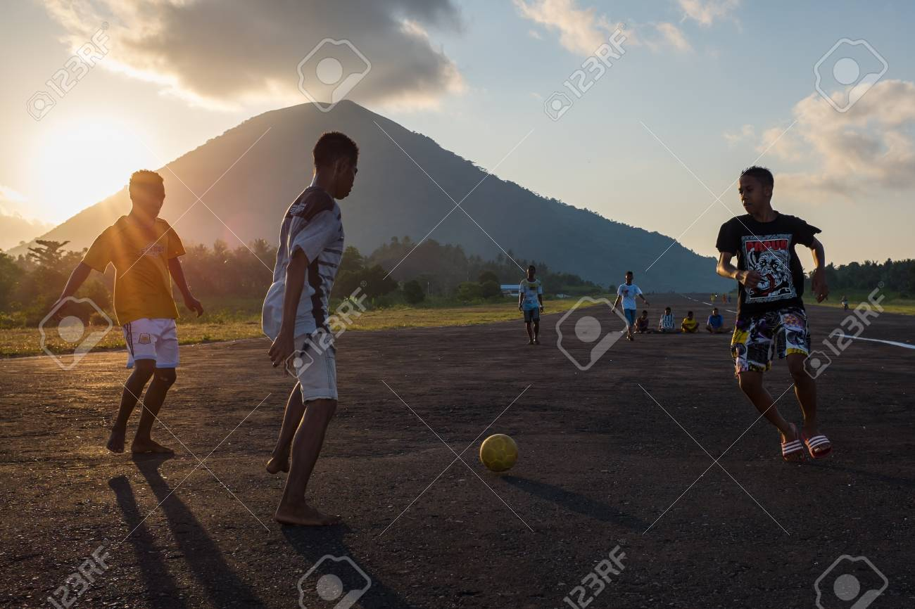 Teenagers play football on the airstrip of Bandaneira with the volcano in the background Standard-Bild - 43484956