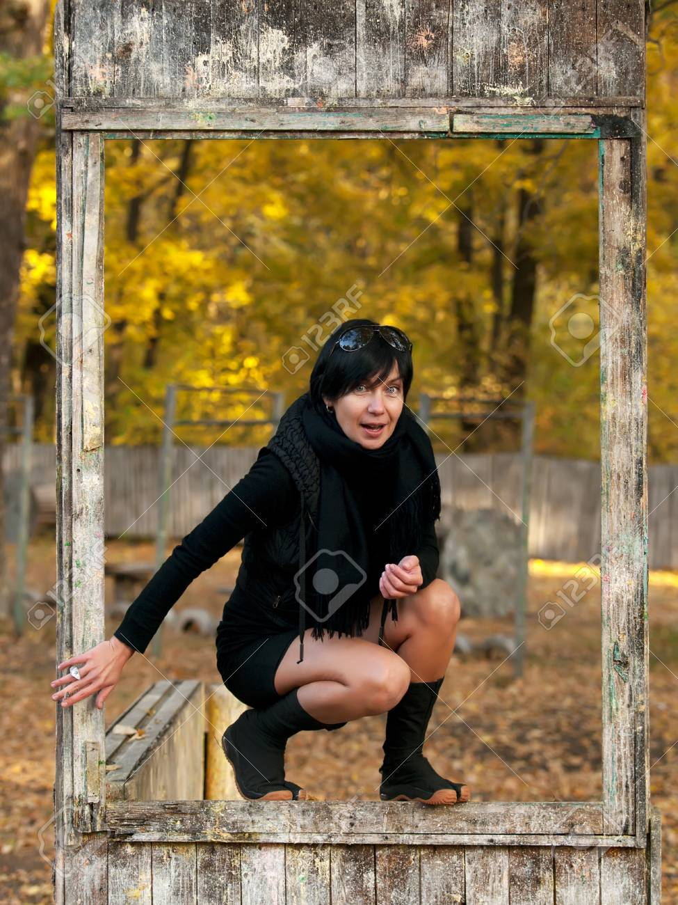 Outdoor portrait of young woman in dirty wooden frame Stock Photo - 7576056