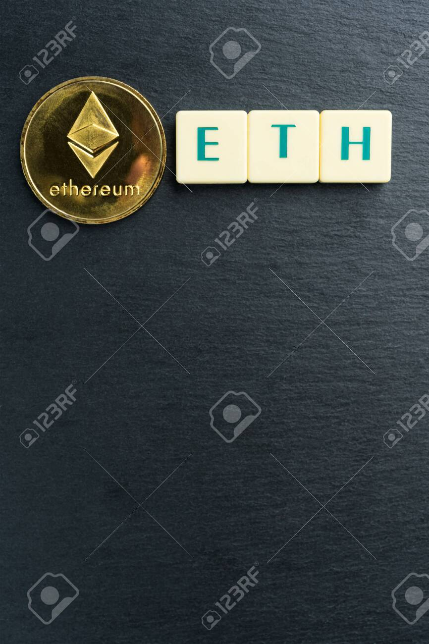 Physical Ethereum gold coin with text made out of letter tiles