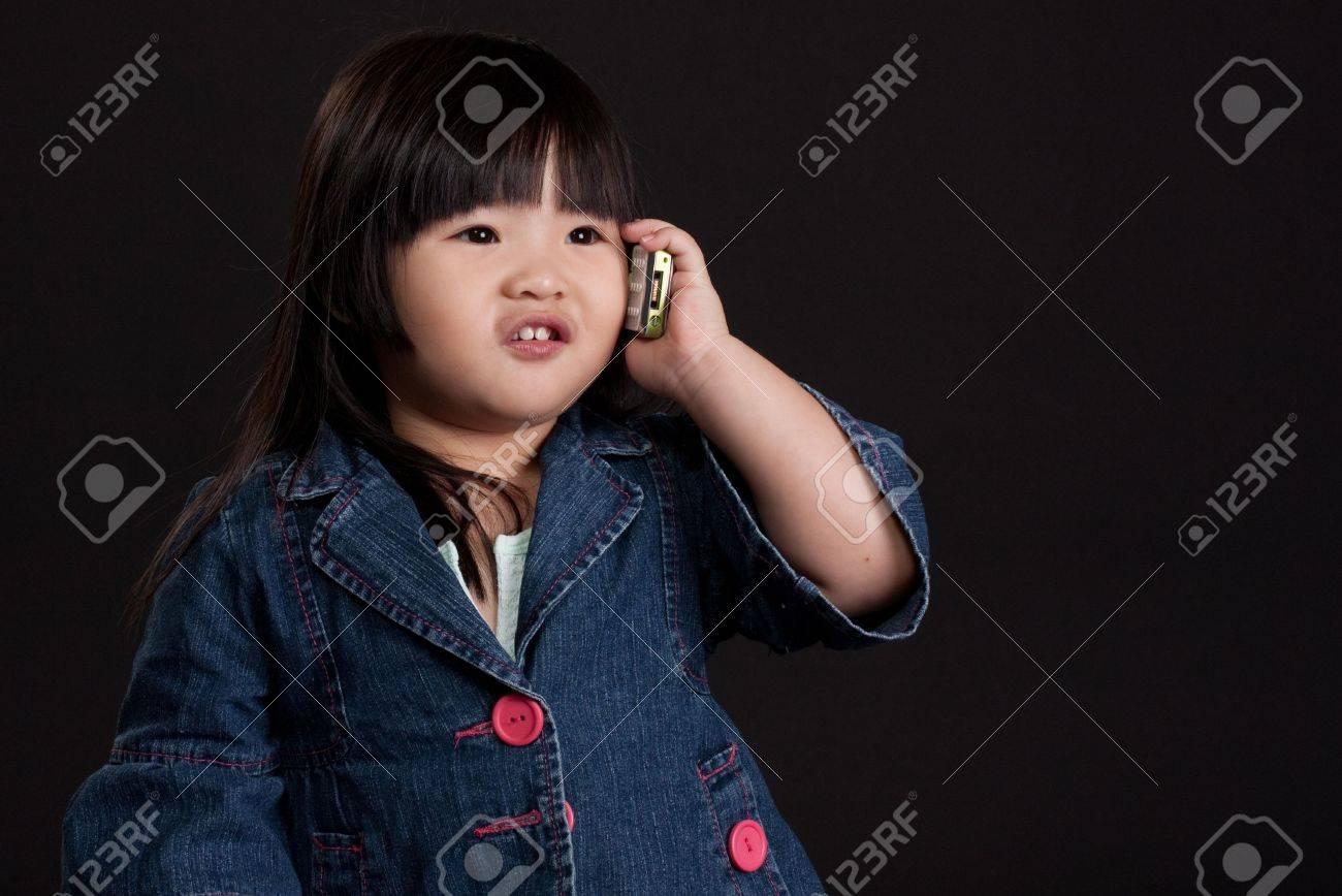 携帯電話を使用して小さなかわいい中国の女の子 ロイヤリティーフリー