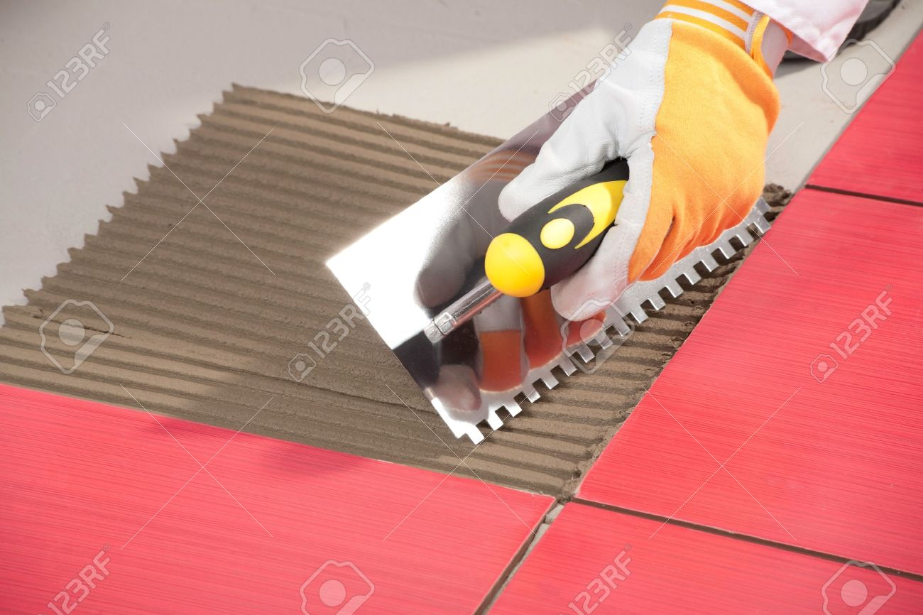 Worker with notched trowel install red tiles with tile adhesive worker with notched trowel install red tiles with tile adhesive stock photo 14329320 dailygadgetfo Gallery