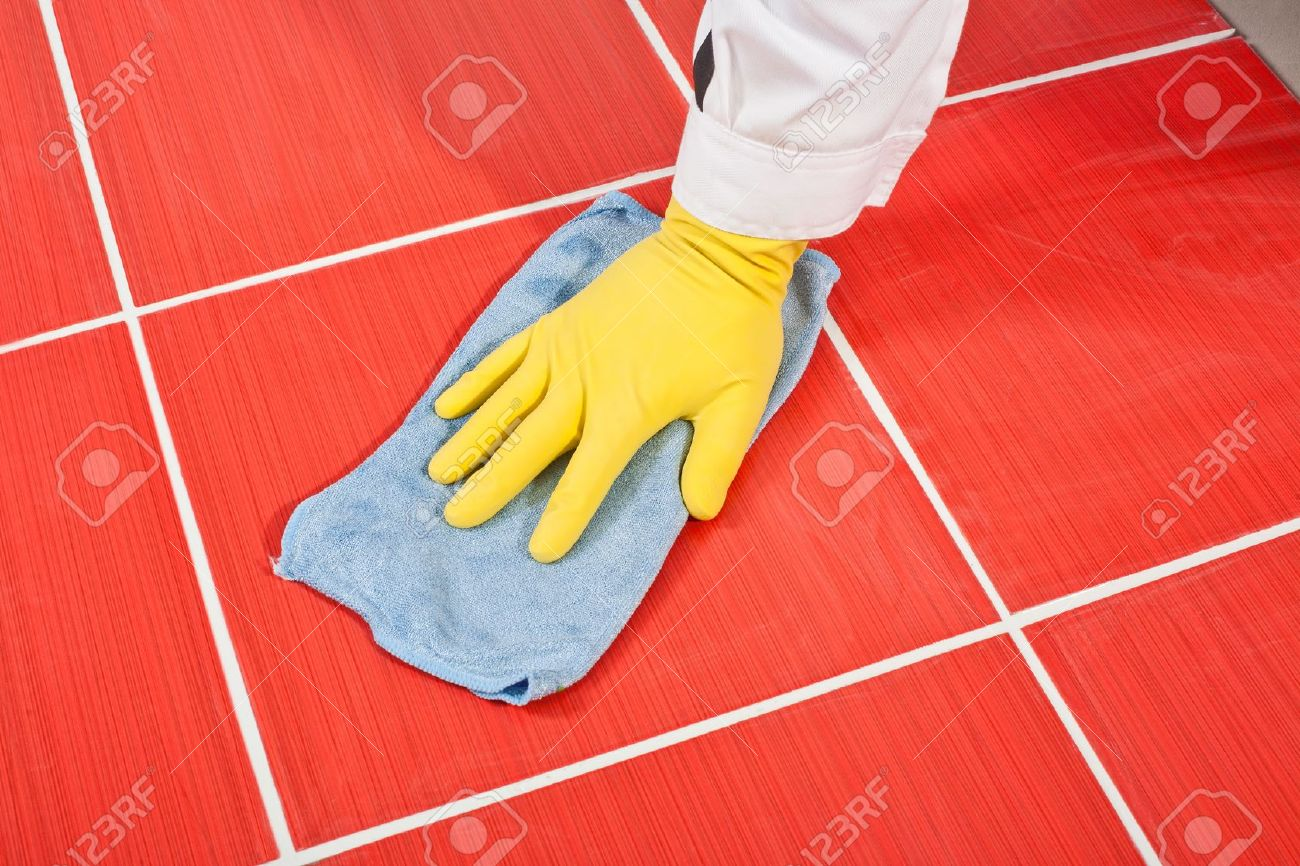 Worker with yellow gloves and blue towel clean red tiles grout Stock Photo - 14329321