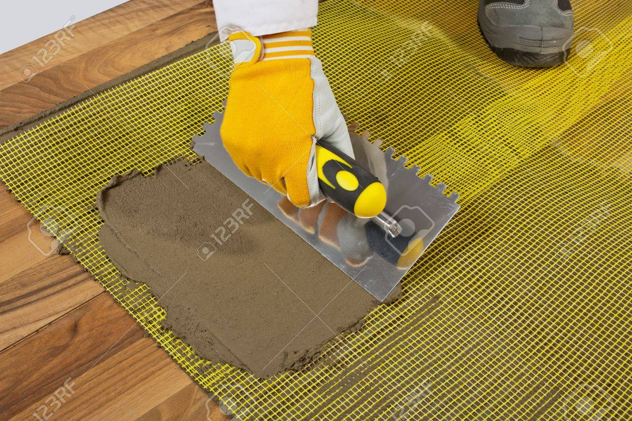 Stock Photo - applies tile adhesive on wooden floor with reinforcement mesh - Applies Tile Adhesive On Wooden Floor With Reinforcement Mesh