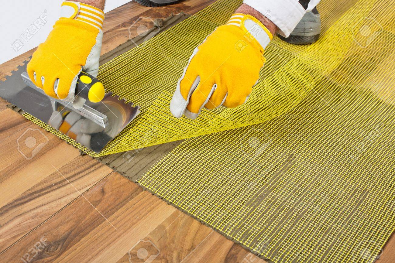 Applying Tile Adhesive With Reinforcement Mesh On Wooden Floor