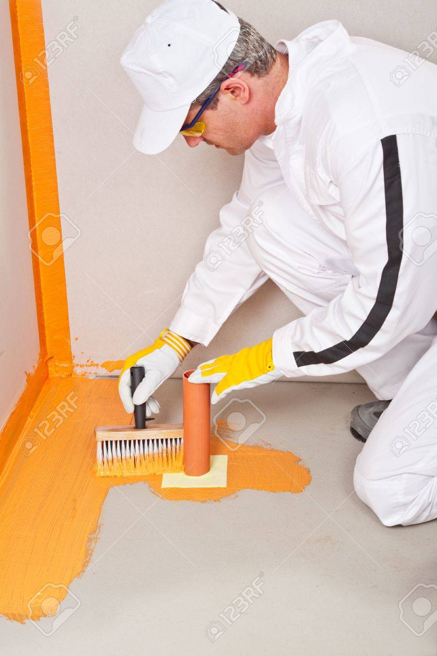 plumber applied waterproofing cuff brush on the floor of the bathroom pipe corner aqueduct channel Stock Photo - 14711137