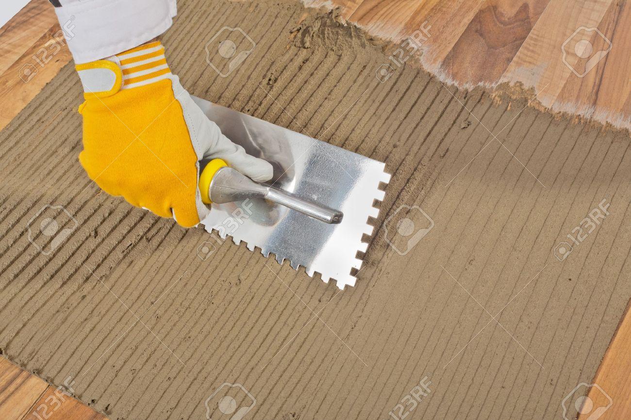 Pavimento Incollato Sul Vecchio lavoratore si è rivolto collante sul vecchio pavimento di legno