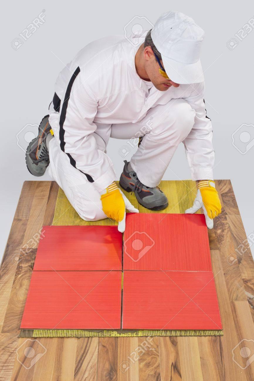 Worker Applies Ceramic Tiles On Wooden Floor With Fiber Mesh Stock ...