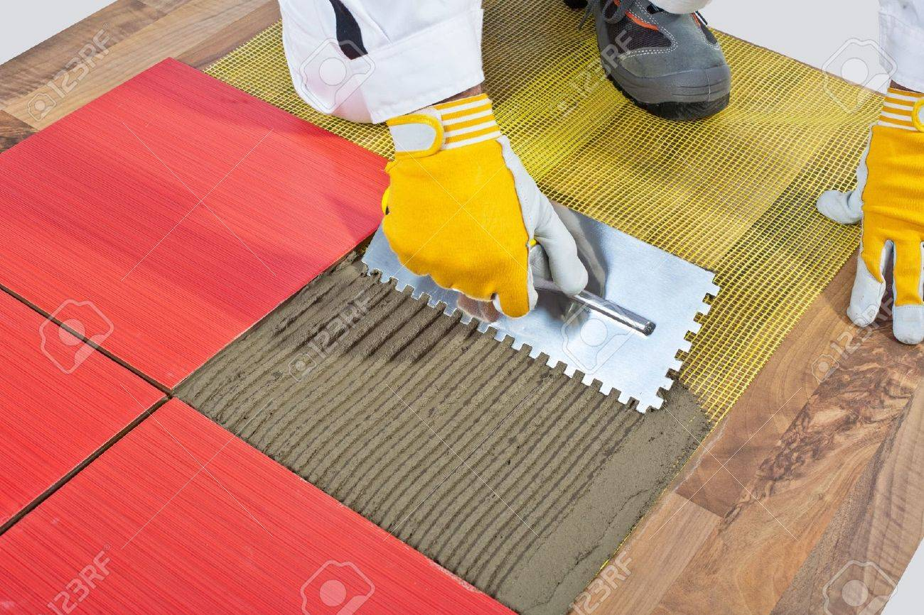 Worker apply ceramic tiles on wooden floor mesh trowel stock photo worker apply ceramic tiles on wooden floor mesh trowel stock photo 14696063 dailygadgetfo Gallery