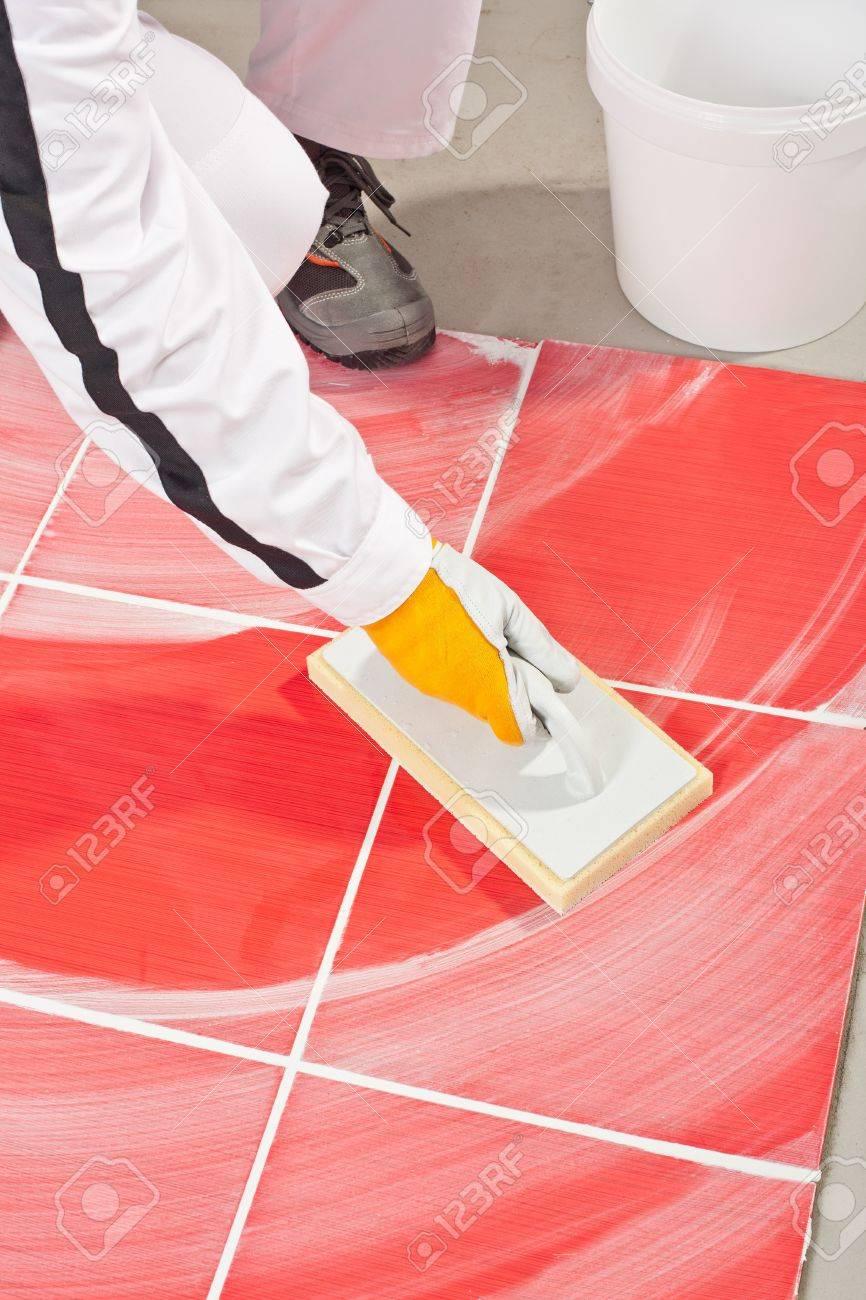 arbeiter mit sauberem schwamm kelle mörtel fliesenfugen lizenzfreie