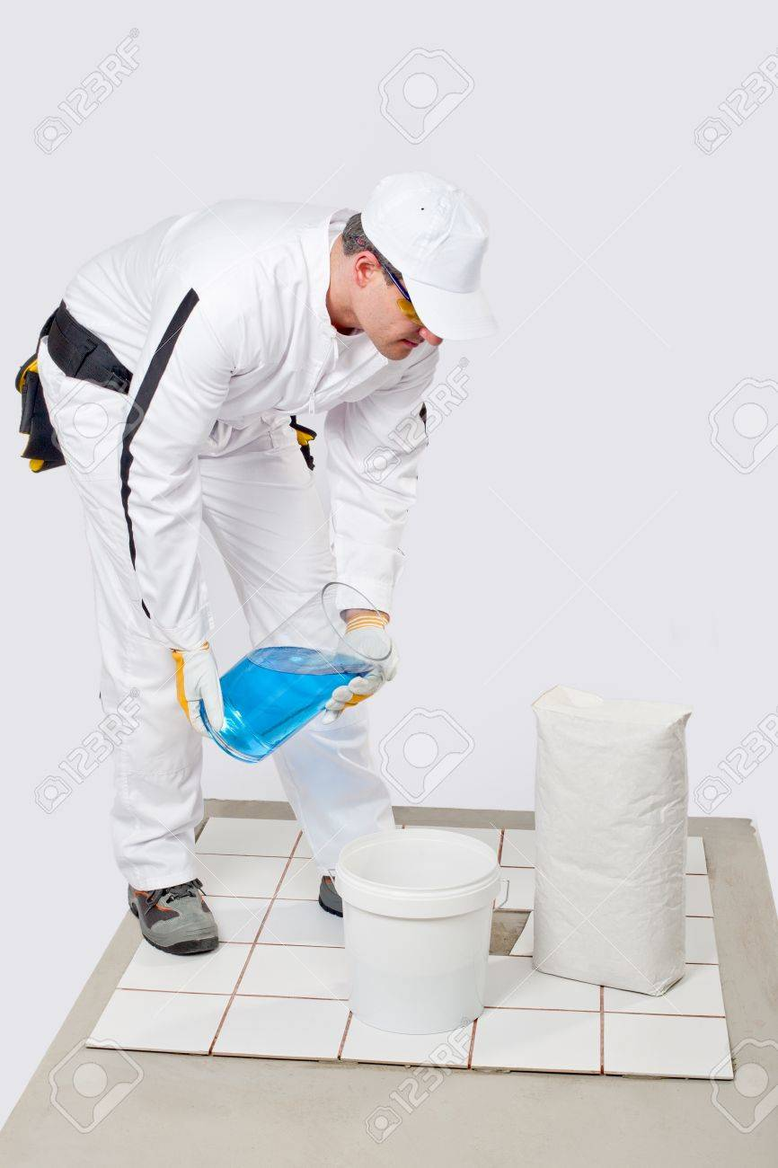 Worker add water to mix tile adhesive in bucket to glue broken white tile on floor Stock Photo - 14711166
