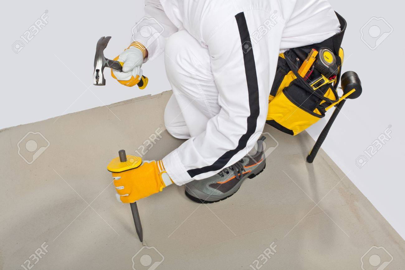 Worker with chisel and hammer check concrete base before tilling Stock Photo - 14669973