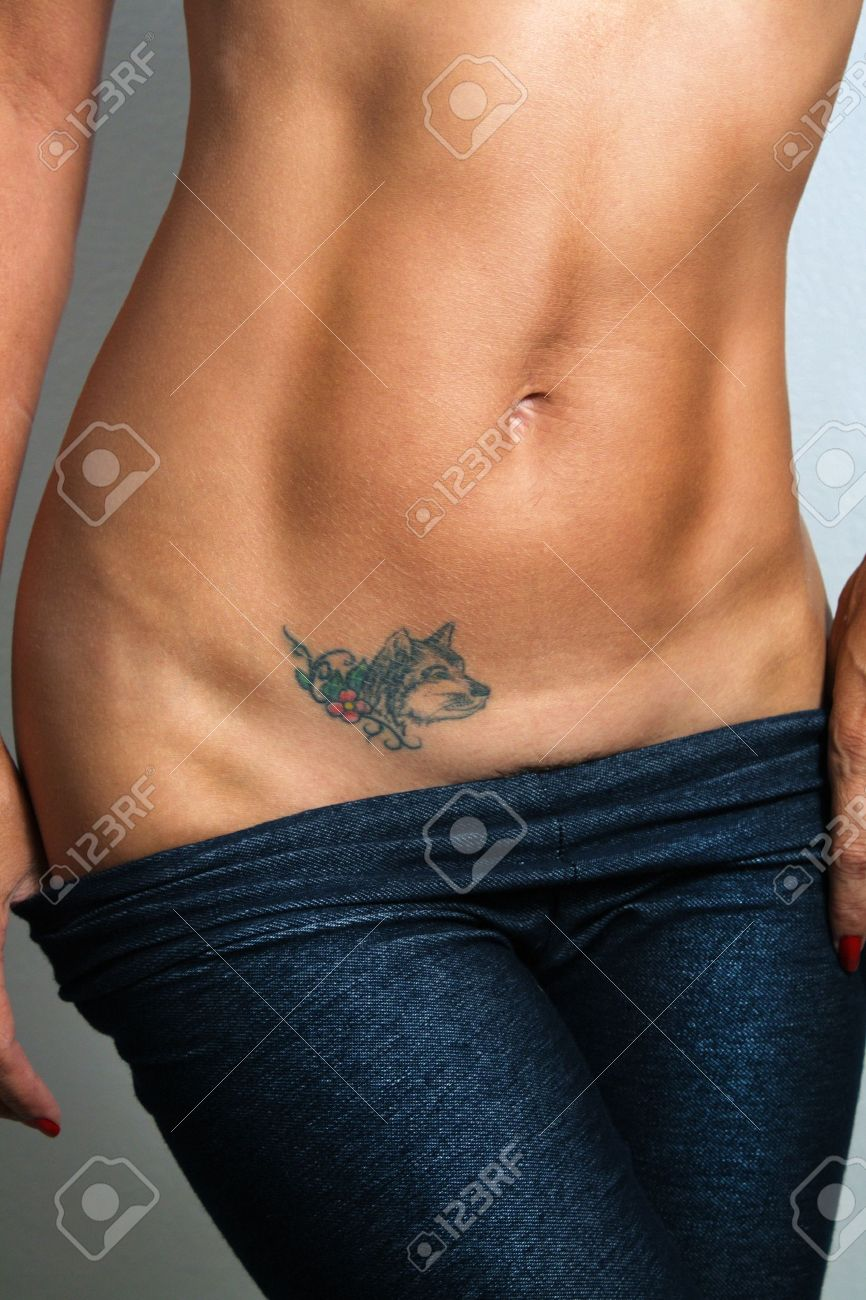 A Sexy Toned Female Abdomen With A Canine Tattoo Stock Photo