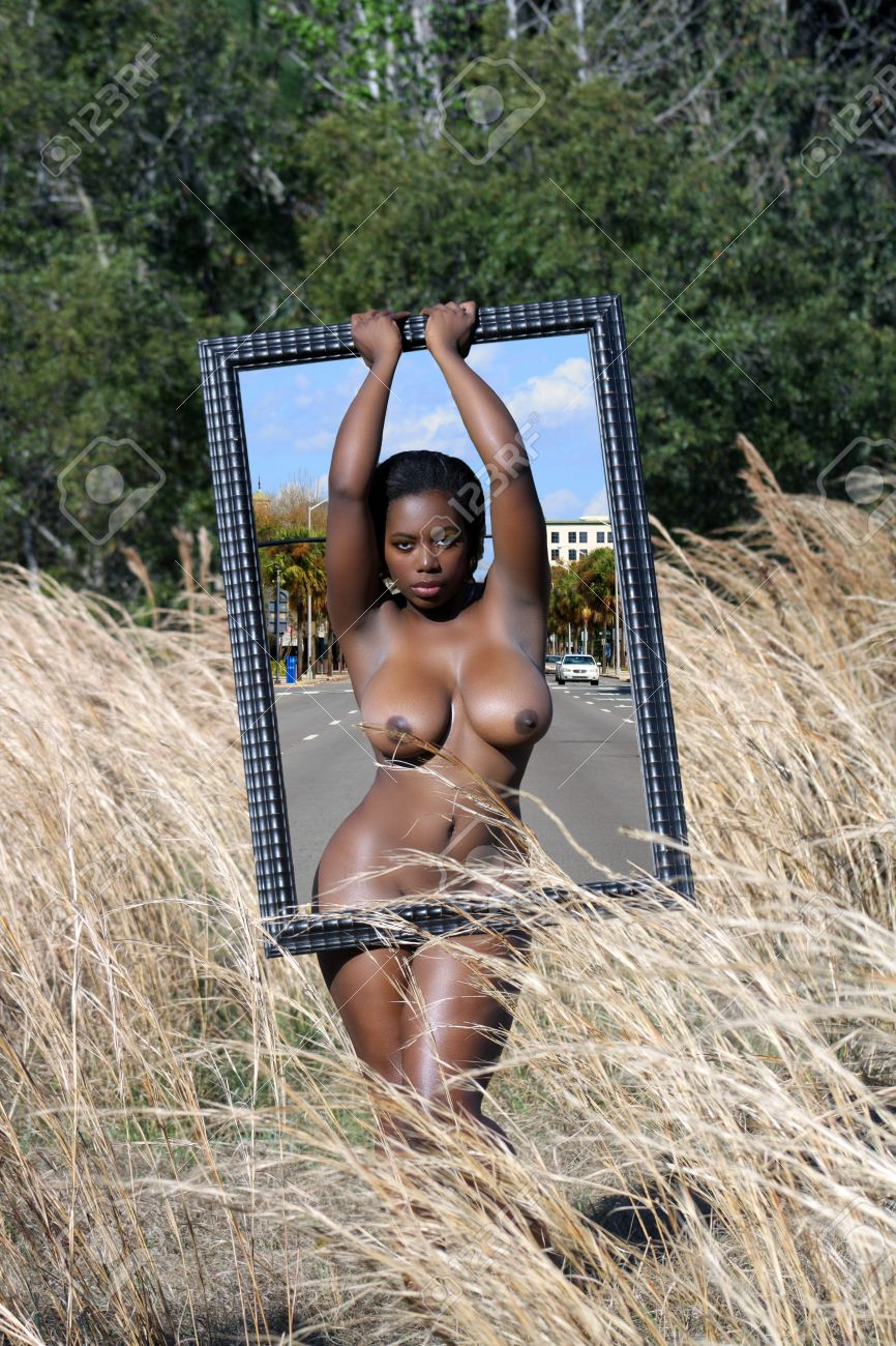 A lovely nude, black woman standing in tall grass holding a large picture frame appears to occupy two dimensions at the same time Stock Photo - 12670426