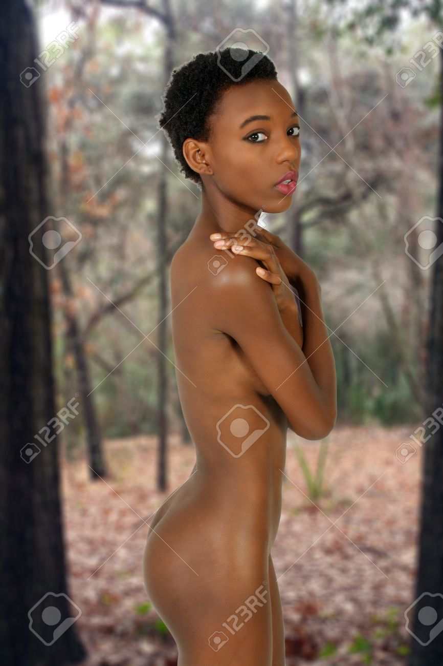 young nudist naked forest A lovely young petite woman, standing, implied-nude in a forest. Stock