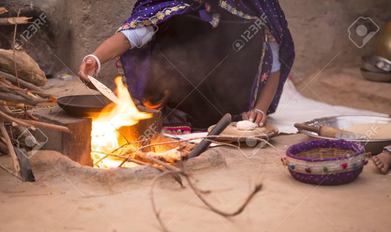 123RF.com & Indian Woman Preparing Chapati In traditional Village kitchen