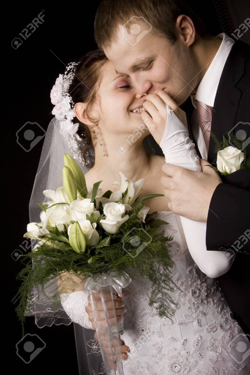 Bride and groom kissing on black background - 4121439
