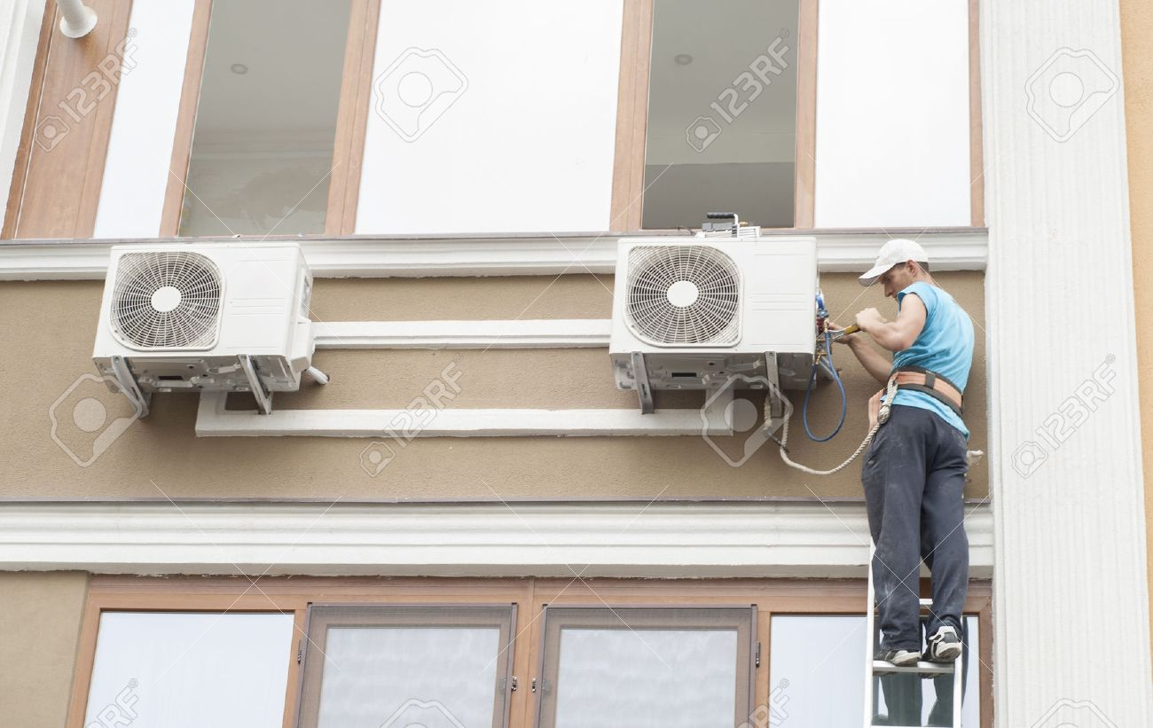 man standing on a ladder and sets the air conditioner outdoor unit - 41885587