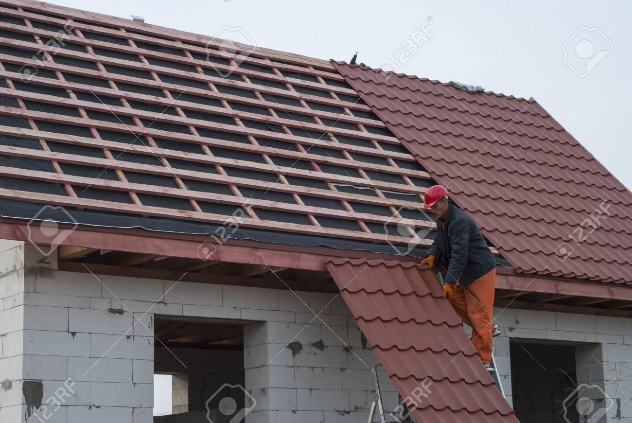 Builder assembles roof tiles of metal - 47701342