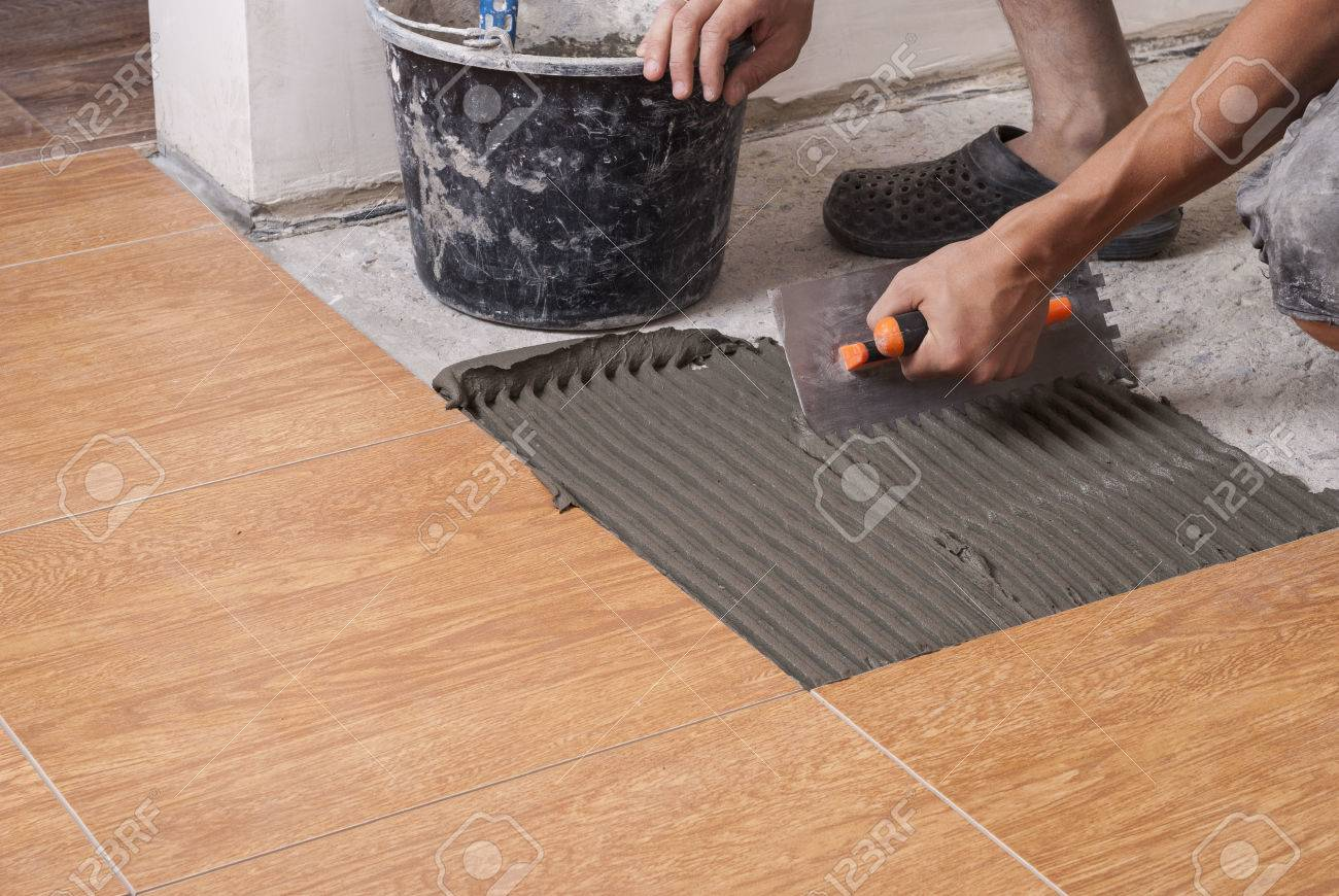 master puts on the floor adhesive for tiling - 65519572