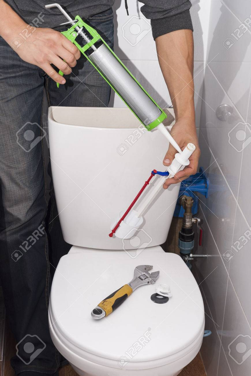 Plumber Repairing The Drain Valve In The Toilet Tank Stock Photo ...