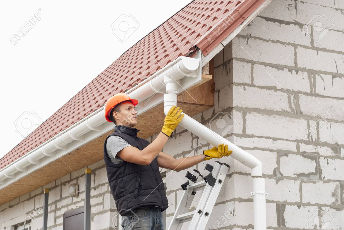 Construction worker installs the gutter system on the roof - 88271393