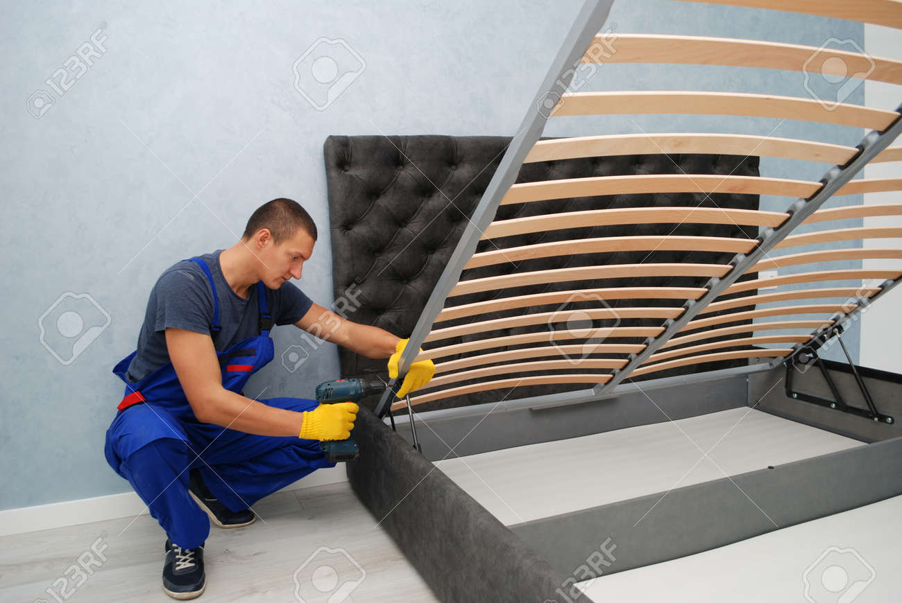 the master is assembling a new bed with a lifting mechanism in the buyer's apartment - 165451318