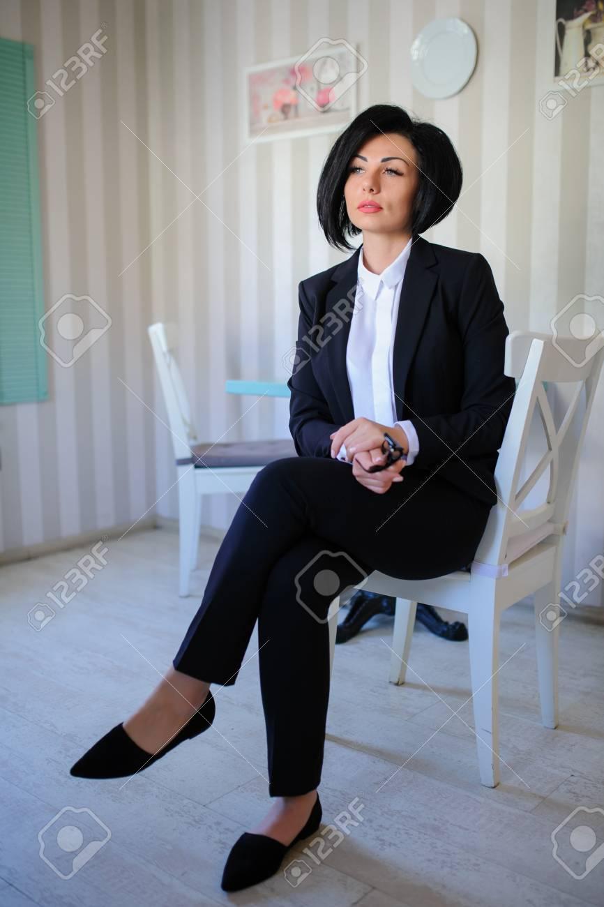 413f895db Bella dama de negocios (mujer   niña) vestida con traje negro sentado en un