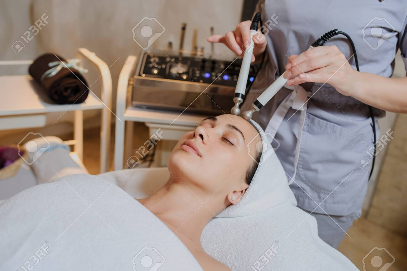 Lateral view of woman facial massage spa procedure. Electric stimulation facial skin care. Microcurrent lift face. Beauty spa procedure. Anti aging rejuvenation non surgical treatment in medical interior room - 151327770