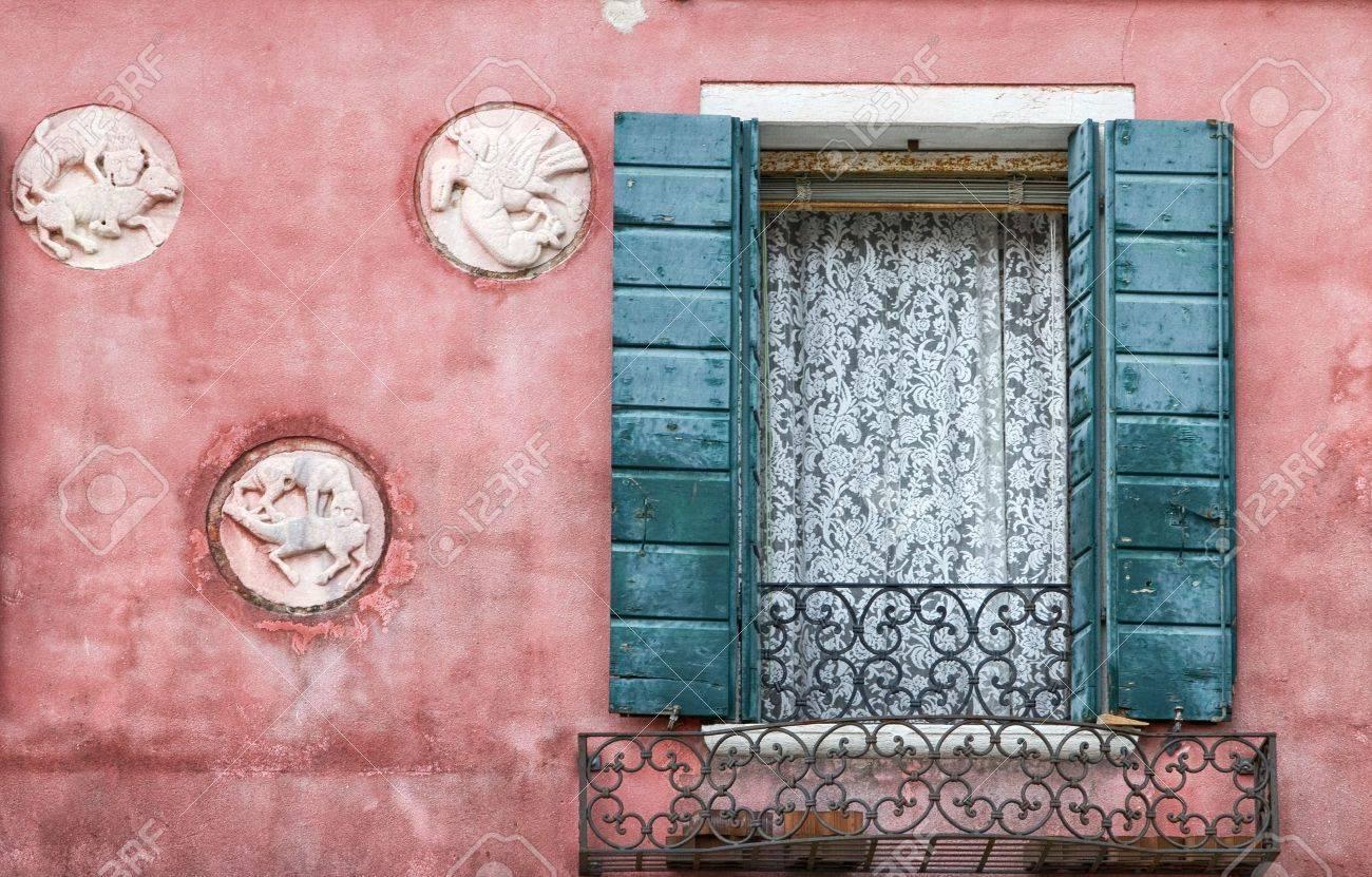 ventana con visillos y persianas en fachada rosa del vintage foto de archivo