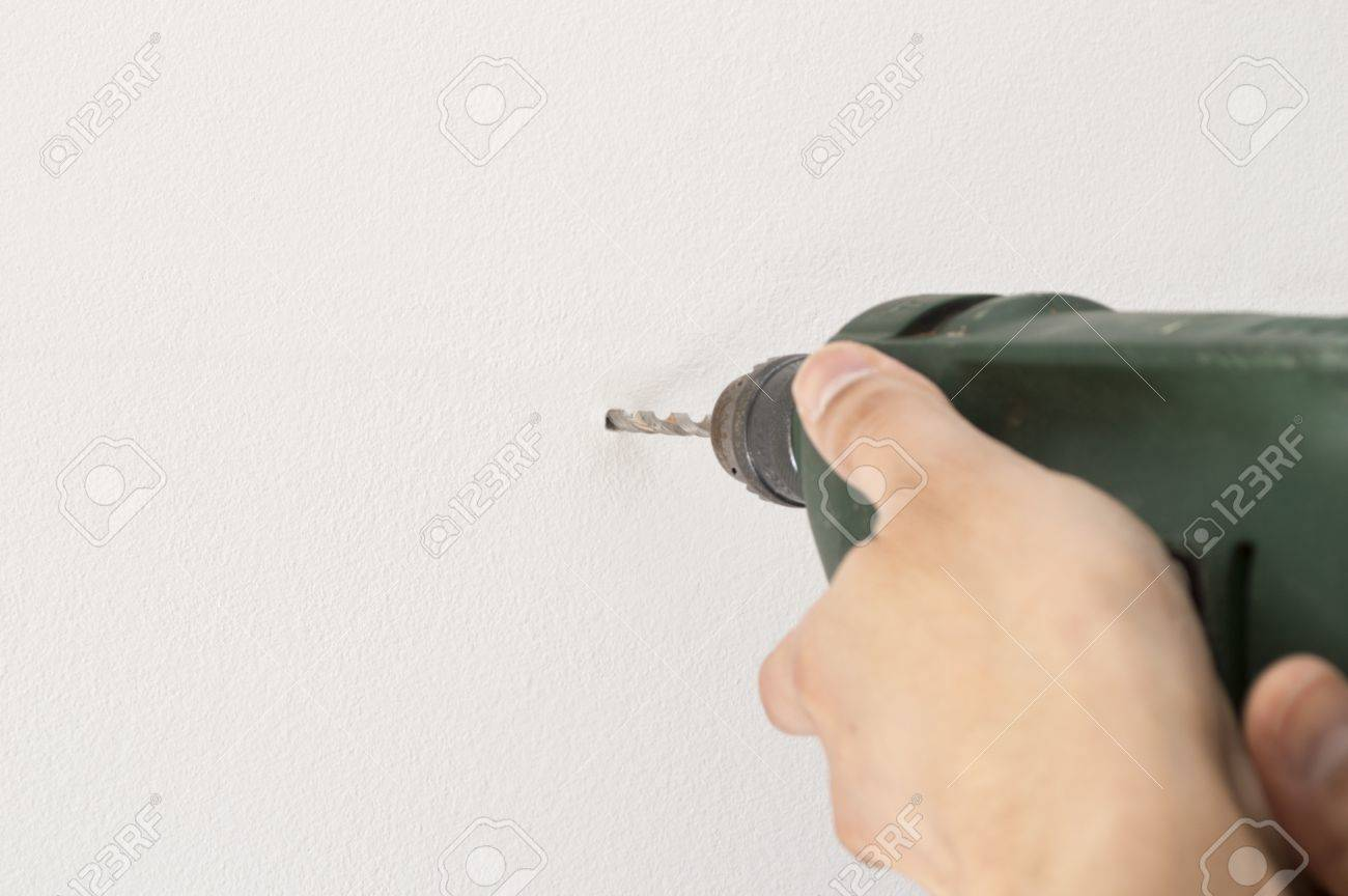 Closeup of a man drilling a hole in wall white and space copy Stock Photo - 18990521