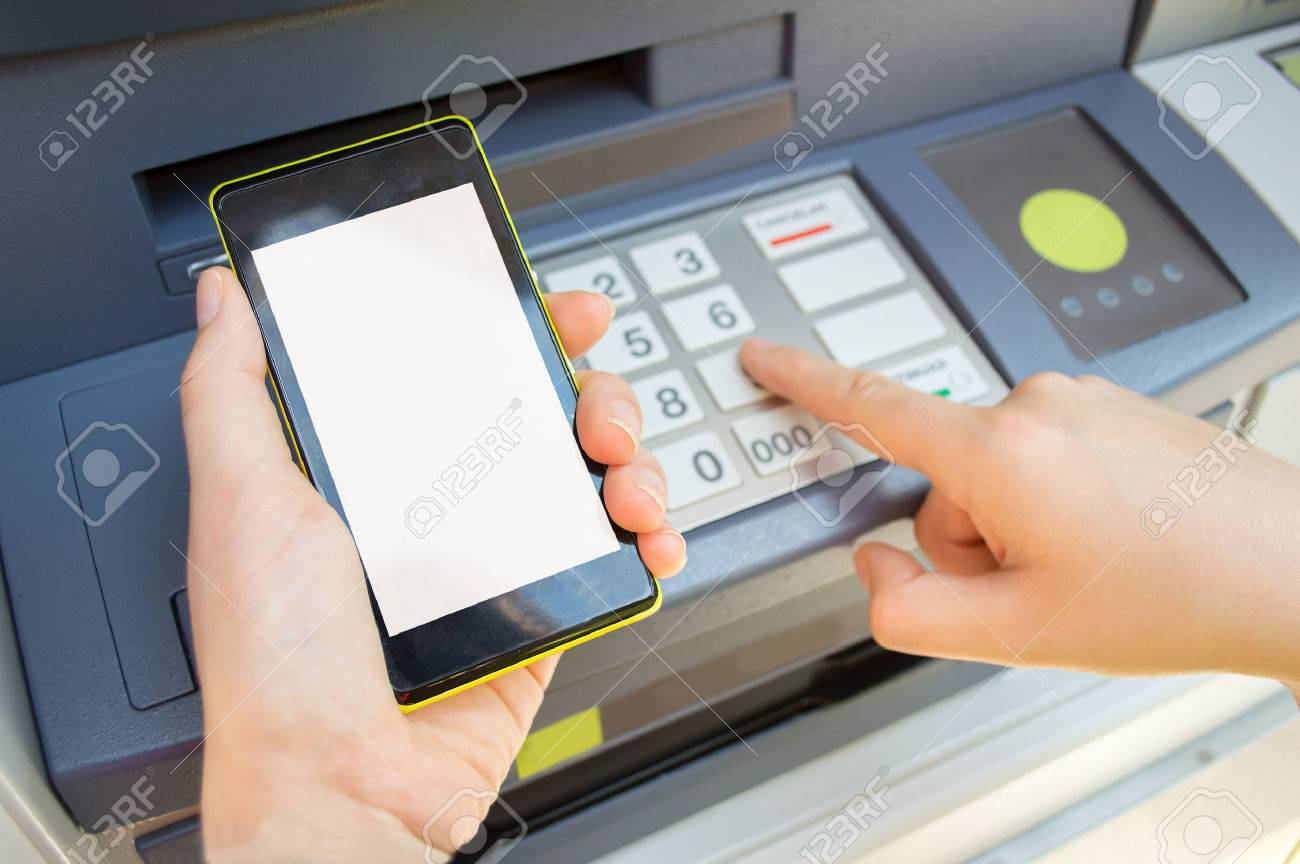 Man typing security PIN code you see on your phone the ATM to