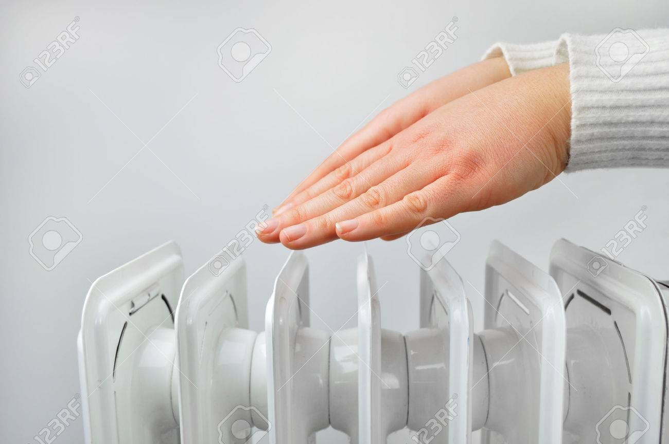 woman gettin warm up her hands over an electric radiator of heating at home  Stock Photo
