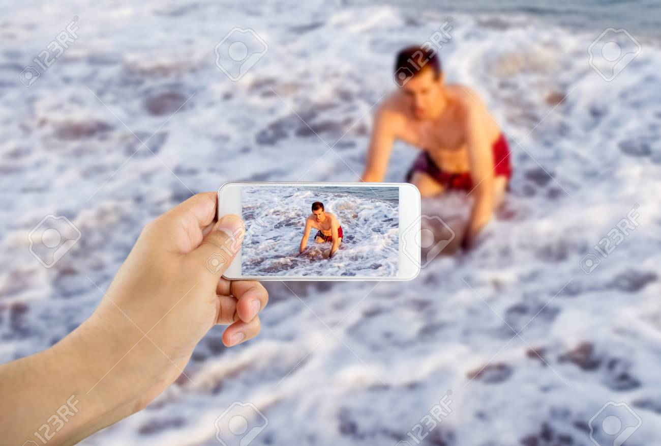 Man filming with his phone as a swimmer drowned