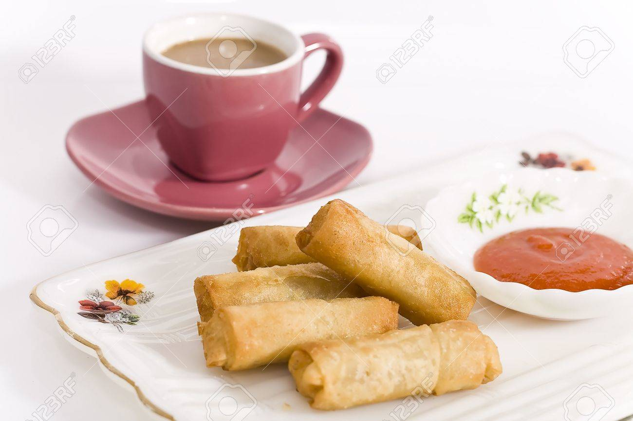crispy fried egg rolls with dipping sauce, served on a plat with a cup of coffee. Stock Photo - 4691448