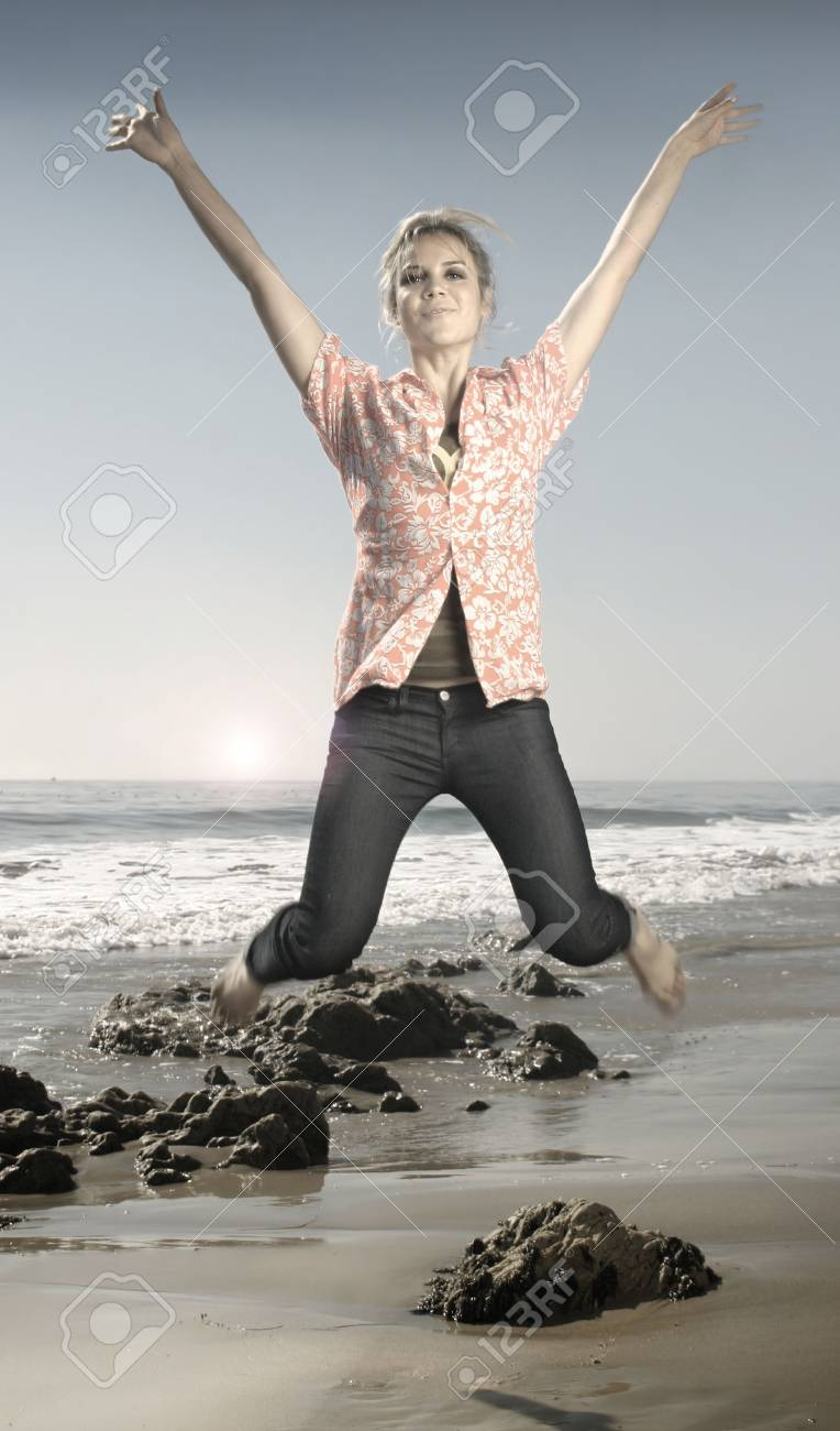 Hip young model jumping in midair on beach Stock Photo - 3780421