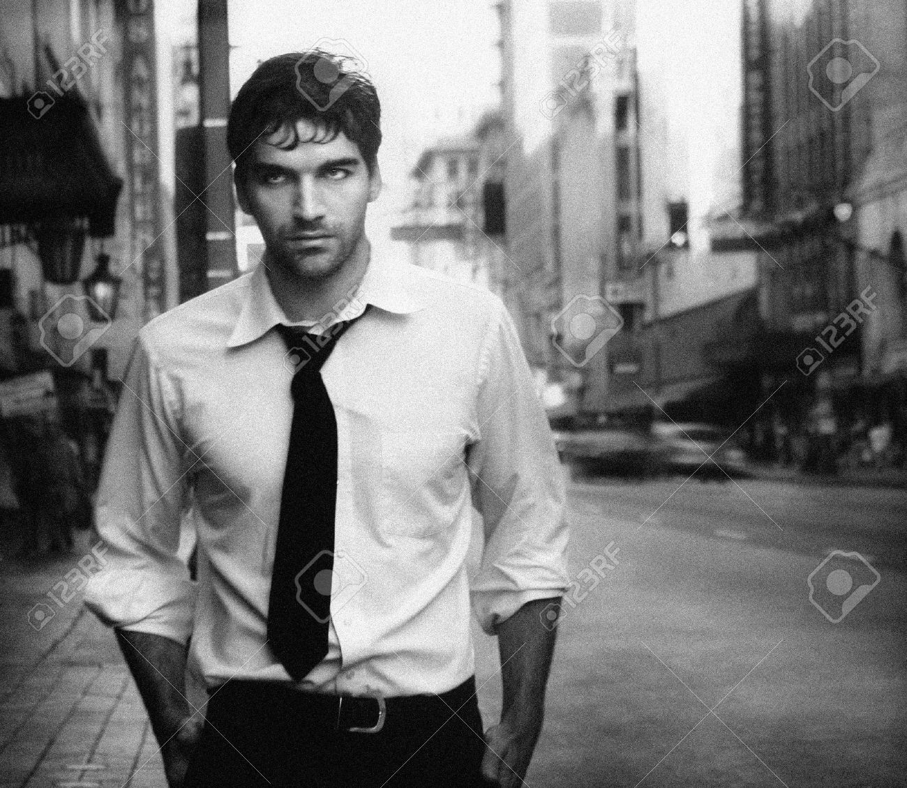 Stock photo vintage stylized black and white photo of young male model against city street photo has an intentional film grain