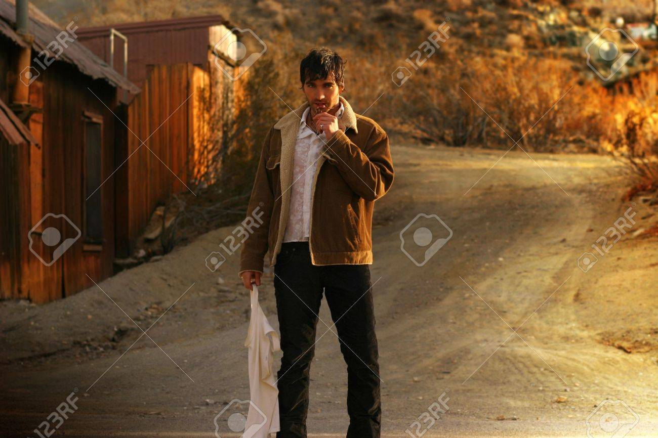 Sexy rugged man standing in the middle of a rural raod Stock Photo - 7498006