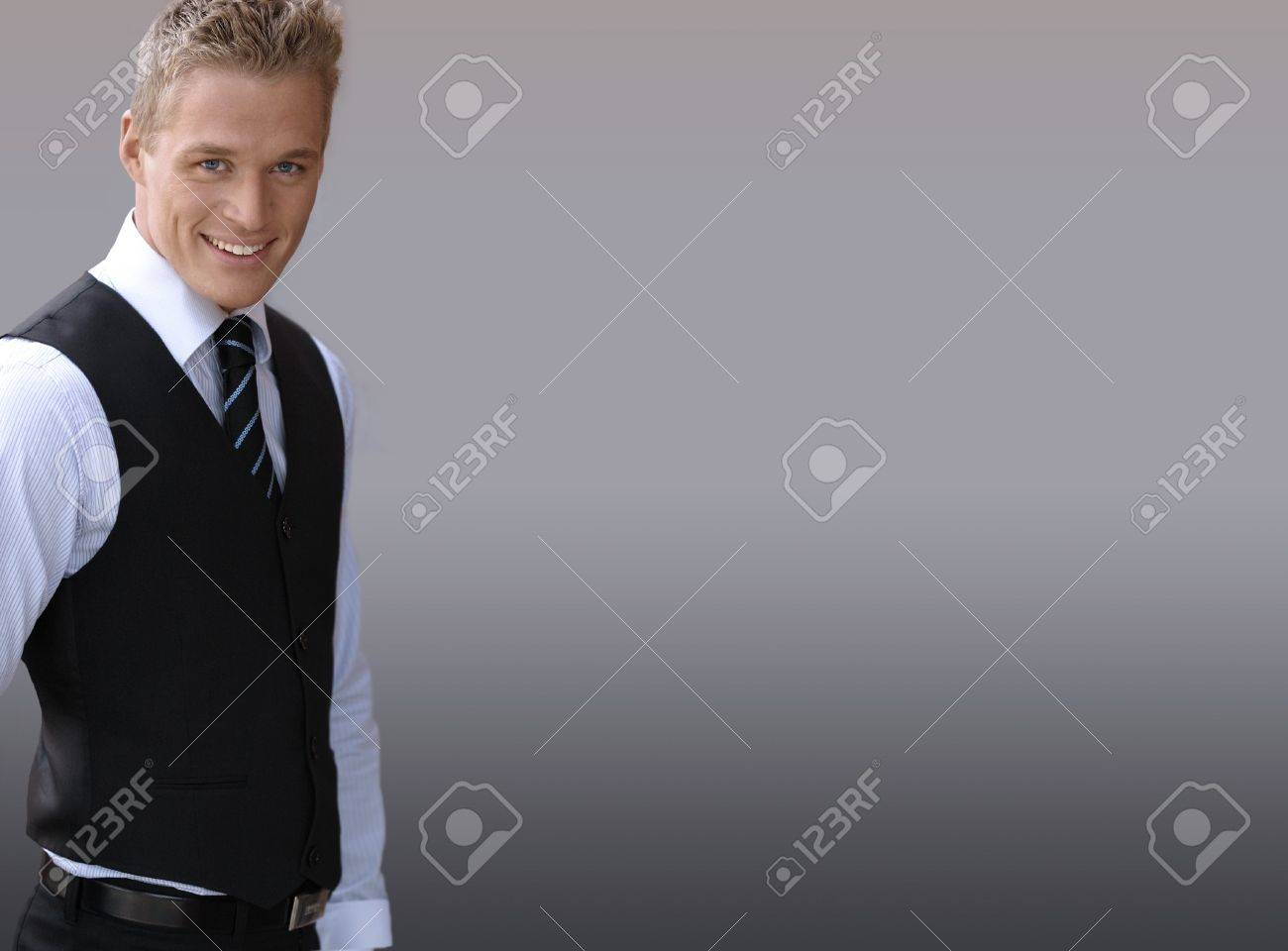 Attractive Smiling Young Businessman Against Neutral Background ...