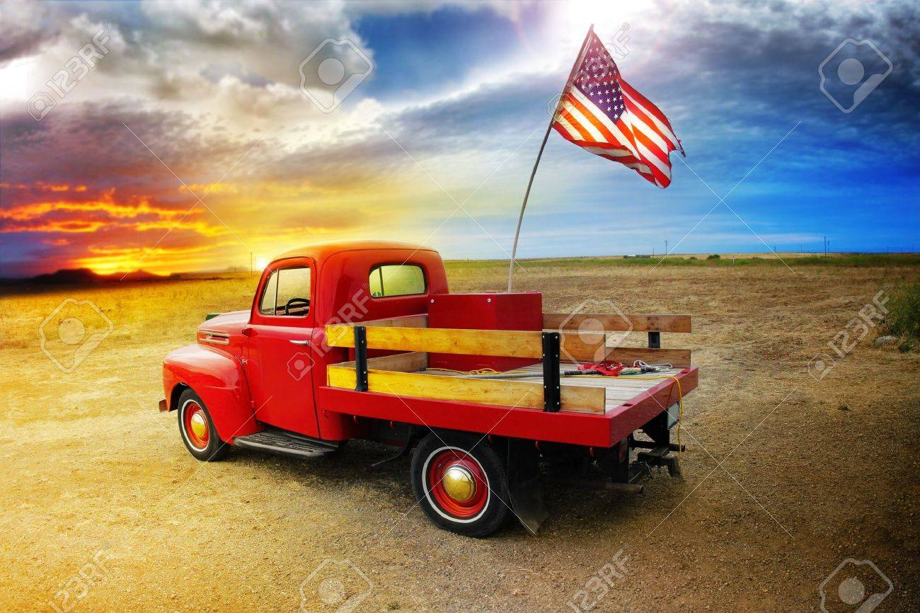 Red vintage pick up truck with American flag in wide open country side with dramatic sunset cloudscape Stock Photo - 8852246