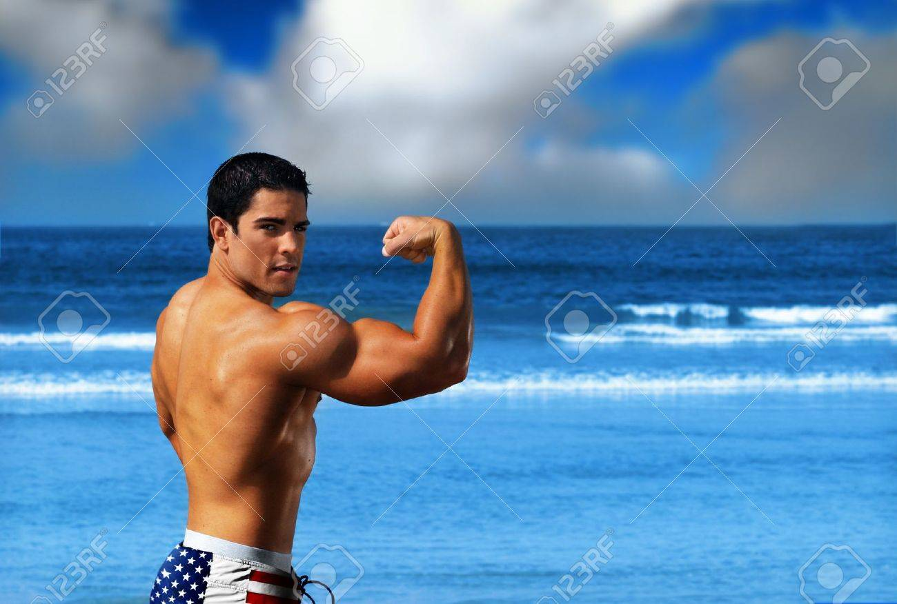 Young muscular sexy male body builder flexing his big bicep on the beach against a bright blue ocean and sky wearing USA flag swim trunks Stock Photo - 9893247
