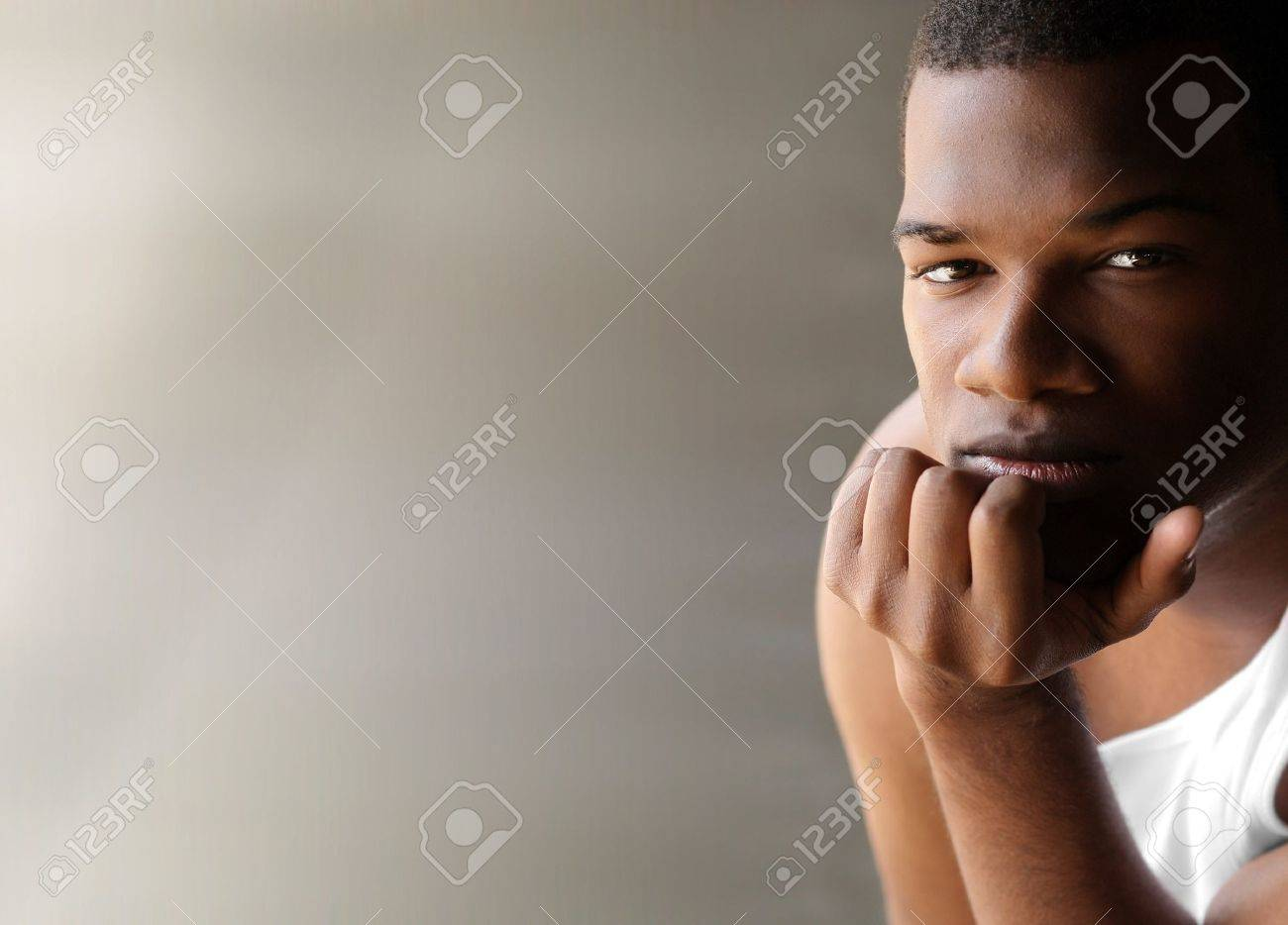 Portrait of a young black man thinking against neutral modern background with copy space Stock Photo - 9893270