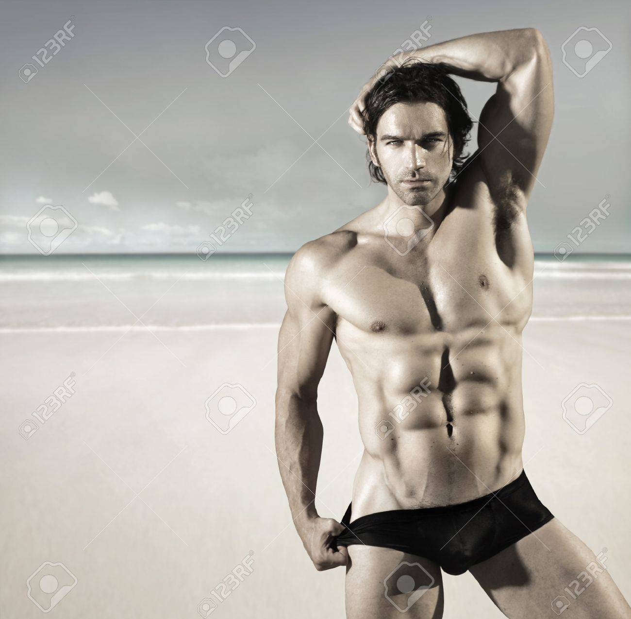 Sexy portrait of a hot buff male fitness model pulling at his bikini briefs on the beach Stock Photo - 12812886