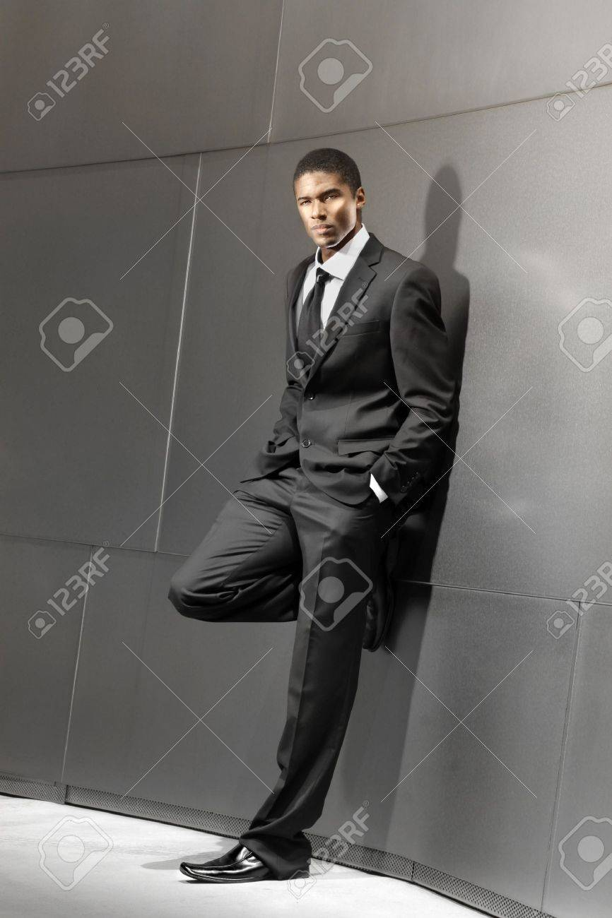 Striking portrait of a young good looking succesful businessman in suit leaning against modern shiny building Stock Photo - 13228993